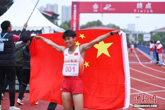资料图为军事五项越野跑比赛结束后中国选手卢嫔嫔举起国旗庆祝。中新社记者 何蓬磊 摄