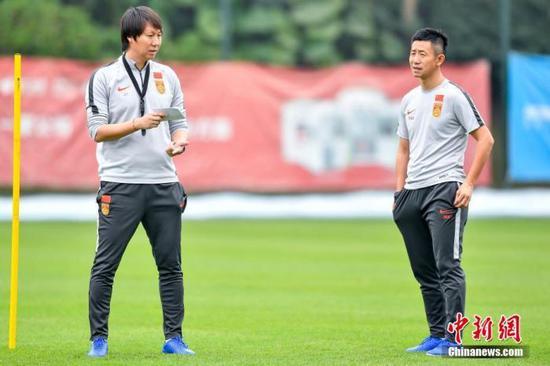 中国国家男子足球队主教练李铁(左)在训练场上规划训练。中新社记者 陈骥旻 摄