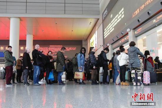 资料图:旅客在排队等待取票。殷立勤 摄