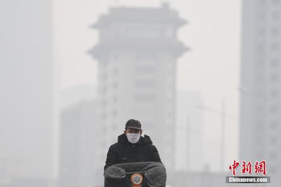 资料图:山西省太原市持续雾霾天气,市民戴口罩出行。中新社记者 武俊杰 摄