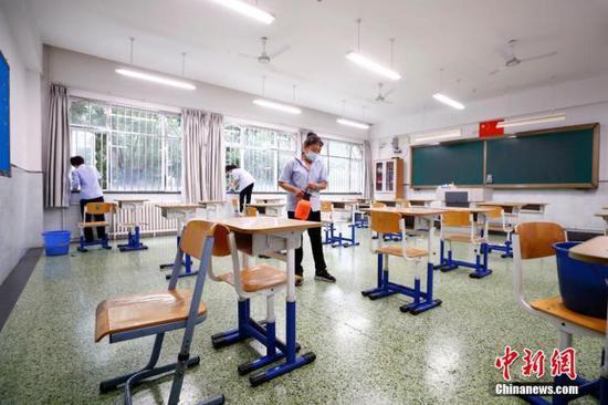 图为7月3日北京十二中保洁人员对考场及走廊进行清扫、消毒。中新社记者 富田 摄