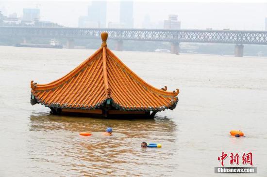 7月10日,湖北武汉,市民游泳经过被洪水淹没的黄花叽亲水平台。受近期强降雨影响,长江中下游干流及两湖出口控制站水位持续上涨,超出警戒水位。中新社记者 张畅 摄
