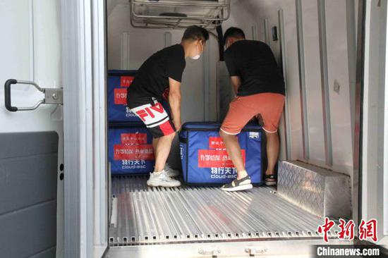 工作人员将60万毫升血液搬运到送血车上。 孙婷婷 摄