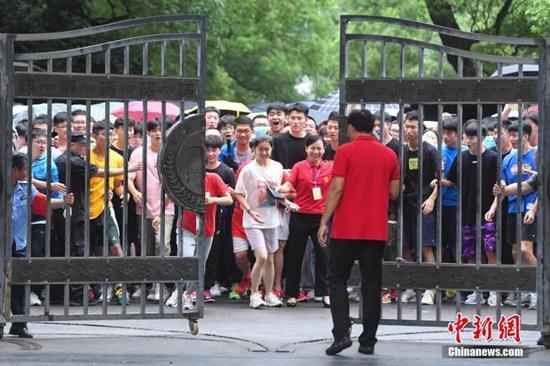 7月8日,长沙市第一中学高考考点的大门打开,结束考试的考生冲出考场。中新社记者 杨华峰 摄