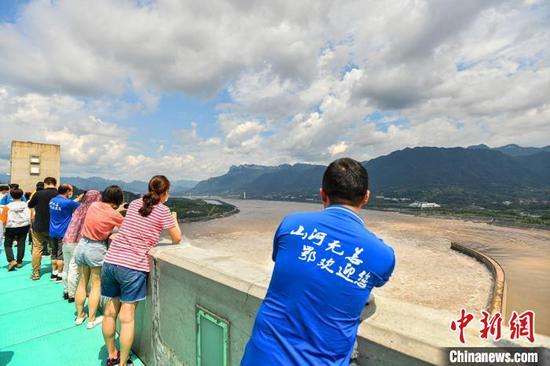 医疗队员们拿出手机拍摄三峡大坝泄洪 钟欣 摄