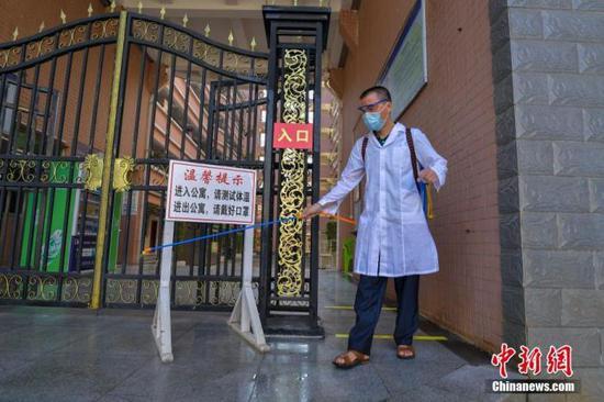 资料图:海口经济学院的工作人员在学生宿舍楼入口消毒。中新社记者 骆云飞 摄