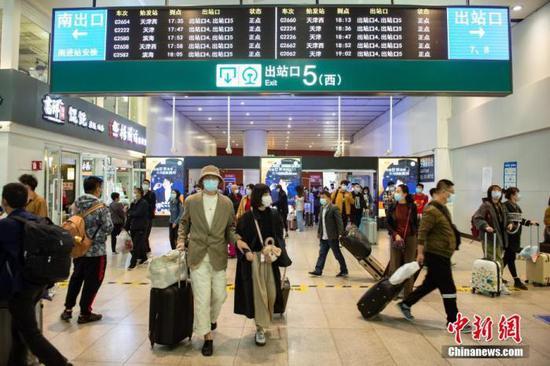 10月8日,旅客走出铁路北京南站5号出站口。当天是国庆假期最后一天,北京南站返程客流增多。中新社记者 田雨昊 摄
