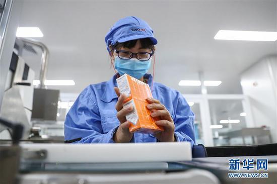 1月6日,科兴中维的工作人员检查新冠病毒灭活疫苗西林瓶装包装线上的包装质量。新华社记者 卢烨 摄