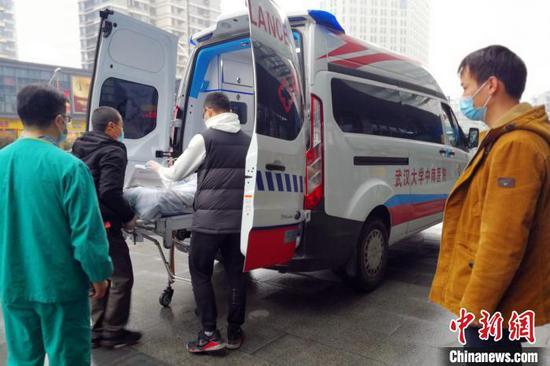 王先(化名)目送父亲被送上转往武汉的救护车 高源 摄