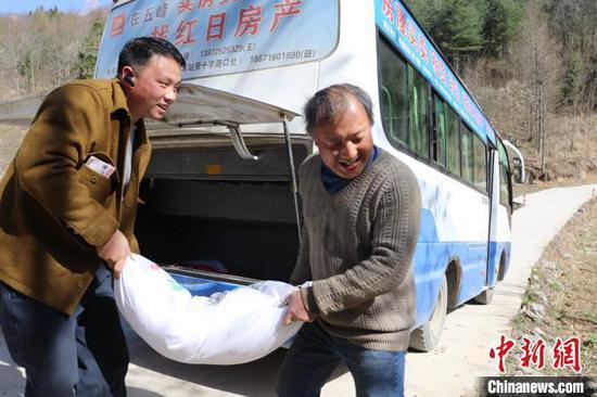 邓兰舟(左)正在帮村民搬运化肥(资料图) 王登府 摄