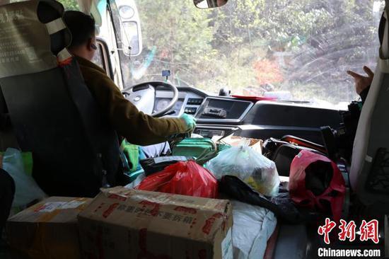 邓兰舟的客车引擎盖上堆满了各种货物(资料图) 王登府 摄