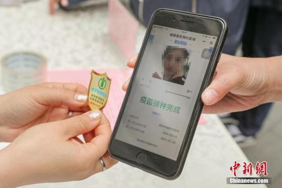 3月29日,北京朝阳门街道在银河SOHO开展新冠疫苗接种集中宣传活动,为辖区楼宇内企业员工发放新冠疫苗接种倡议书和手机贴。中新社记者 贾天勇 摄