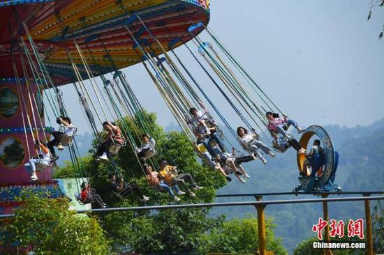 """5月1日,""""五一""""节假的第一天, 重庆涪陵红酒小镇景区内的游客乘坐体验游乐设施。 中新社记者 陈超 摄"""