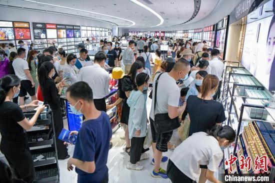 图为游客在三亚国际免税城选购化妆品。 骆云飞 摄