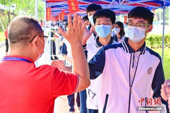 6月7日,广东省广州市南沙一中考点,老师与考生击掌为考生加油。中新社记者 陈骥旻 摄