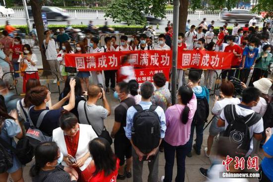 6月7日,北京人大附中考点外,送考同学为考生拉横幅加油。中新社记者 富田 摄