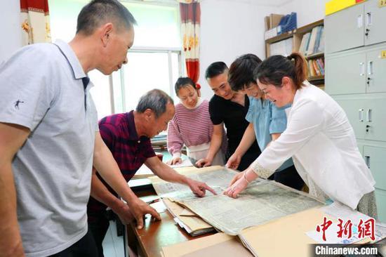 马良云(左二)分享收藏的书刊 陈黄奎 摄