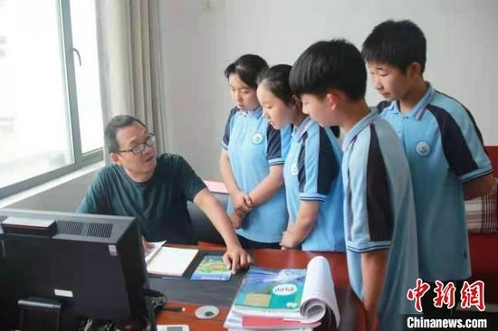 祝习军在办公室辅导学生(资料图) 聂志远 摄