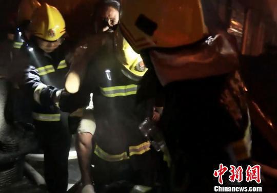 消防员将被困职员背离火灾现场 刘芳琳 摄