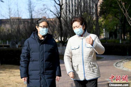 图为中国工程院院士、国家卫健委高级别专家组成员李兰娟(右)和助手在一起。中新社记者 安源 摄