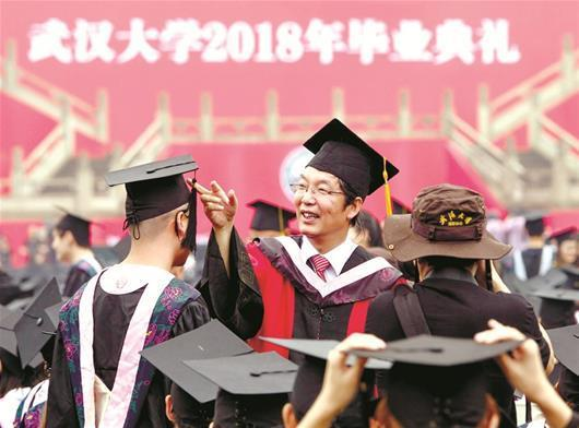 图为:6月22日,导师冒雨给武汉大学毕业生拨穗 楚天都市报记者萧颢宋枕涛摄