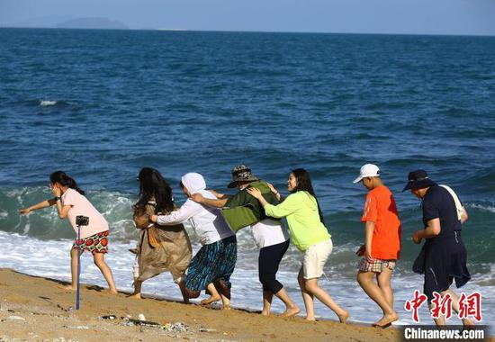 5月3日,游客在三亚南山文化旅游区海边游玩。 陈文武 摄