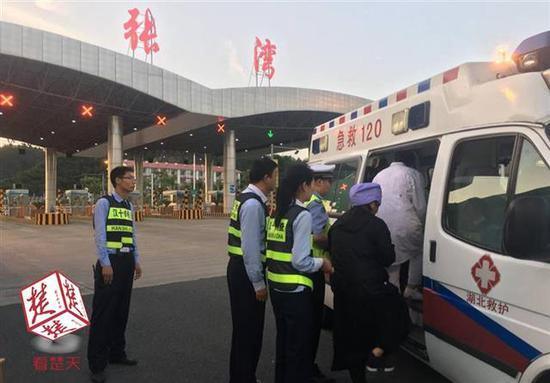 收费站工作人员帮忙将患病司机送上救护车辆