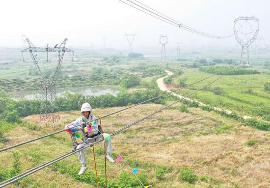 胡洪炜在超高压线路上带电作业。新华社记者 侯文坤 摄