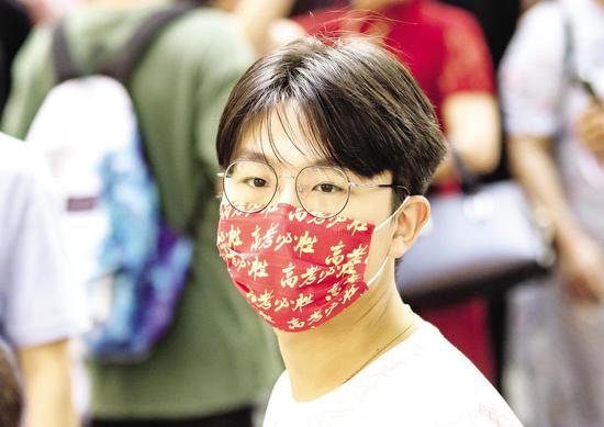 """6月7日,武汉市第二中学考点,一名考生戴着""""高考必胜""""字样的口罩走进考场。 (湖北日报全媒记者 柯皓 摄)"""