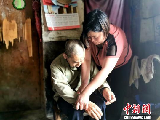 梁国玉正在为养父的哥哥整理衣服 胡传林 摄