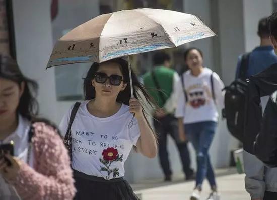 17日午后,市民行走在艳阳下。记者周迪摄