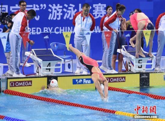 图为中国队第三棒张雨霏和第四棒杨浚瑄在比赛中交接棒。中新社记者 侯宇 摄