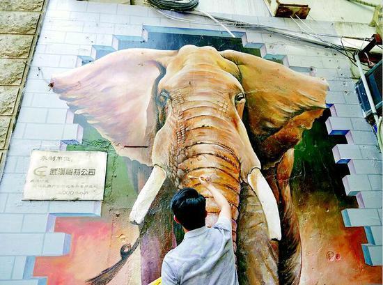 图为:郭剑在江汉路上绘制的大象似乎要破墙而出