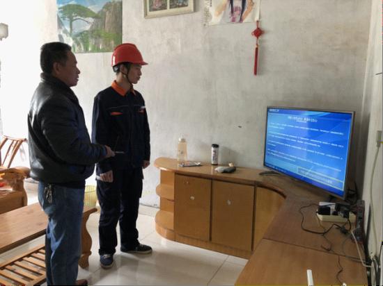 电信员工指导村民张昌发使用新功能