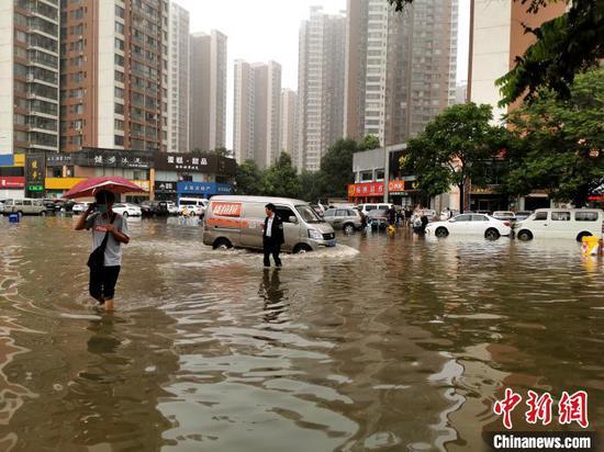 襄阳市汉津路渍水,居民徒步趟水上班 胡传林 摄