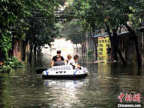 辖区道路渍水,襄阳市七里桥社区利用橡皮艇接送居民出行 姚莹 摄