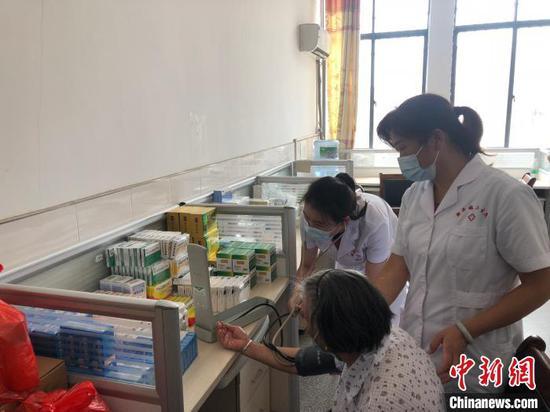 在安置点的医务室,护士为老人量血压 梁婷 摄