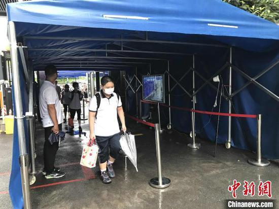 10日清晨,武汉二中广雅中学学生经过测温通道进入校园 张芹 摄