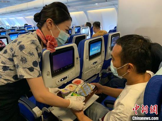 乘务员向旅客提供热餐。东航供图