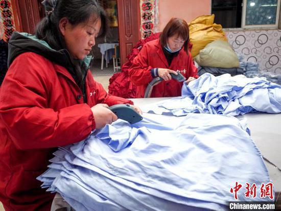 图为武汉加十分服装工厂的女工正在熨烫布料 张畅 摄