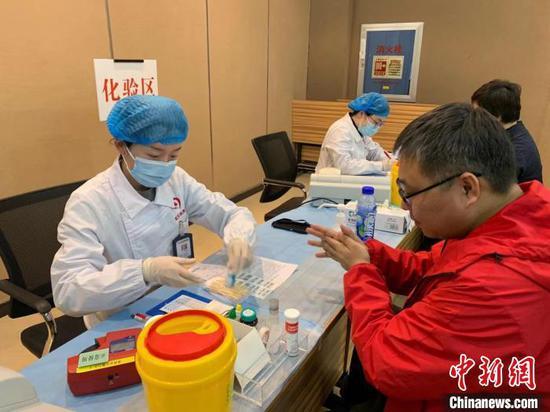 图为内蒙古援鄂医疗队员正在进行献血前的消毒 武一力 摄