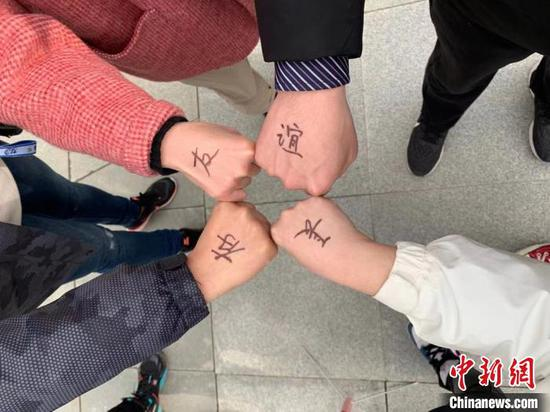 """图为援鄂医疗队员们在手背上写着""""友谊长存"""" 武一力 摄"""