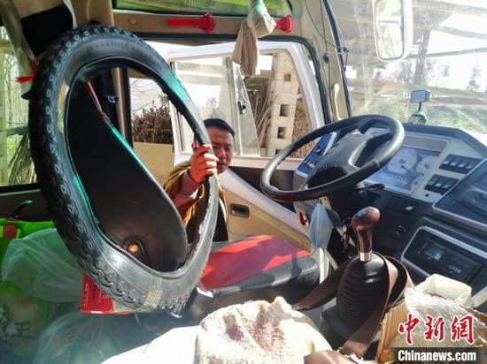 邓兰舟正在从车上取下帮村民带回的轮胎(资料图) 王登府 摄
