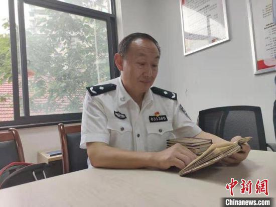 图为民警杨远高翻看过去侦办案件笔记 孙逊 摄