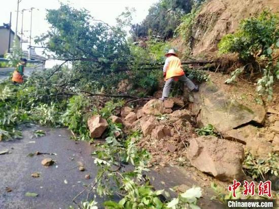 降雨引发道路塌方,公路养护人员及时清障。 陈琦 摄