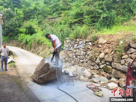 当地干部群众开展灾后道路清障保畅工作。 陈琦 摄