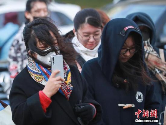 资料图:民众在大风降温天气中出行。中新社记者 贾天勇 摄