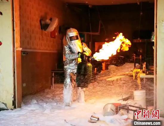 消防员火中徒手拎出着火煤气罐。湖北咸宁消防供图