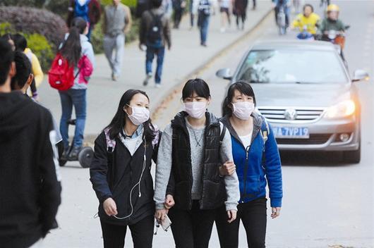 图为街头的姑娘们戴着口罩遮挡被风吹落的梧桐絮。
