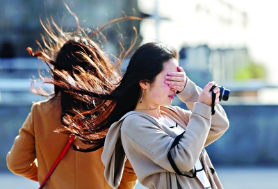 一名女生在汉口江边被风吹得睁不开眼                 记者任勇 摄